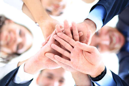 Small group of business people joining hands, low angle view Stock Photo
