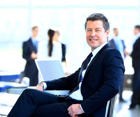 Casual businessman working in office, sitting at desk. photo