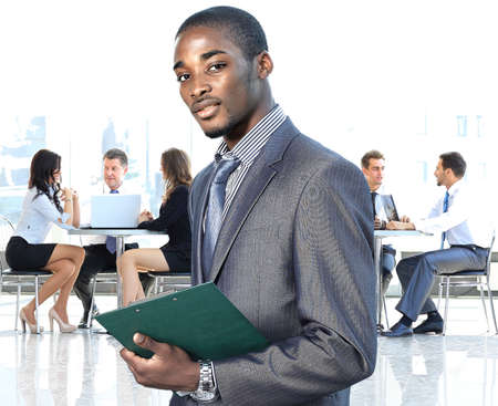 african businessman: african american businessman in modern office with colleagues on background