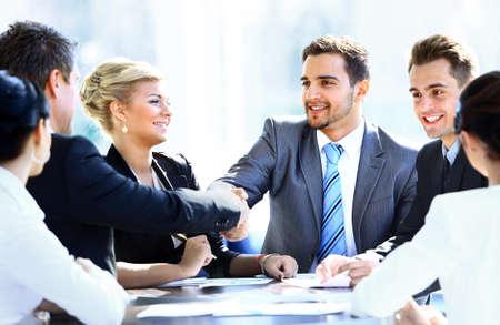 empresas: Colegas de negocios sentado en una mesa durante una reunión con dos ejecutivos hombres dándose la mano Foto de archivo