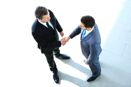 to the top: Top view of a two businessman shaking hands - Welcome to business