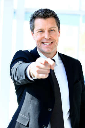 Handsome businessman pointing his finger at you photo