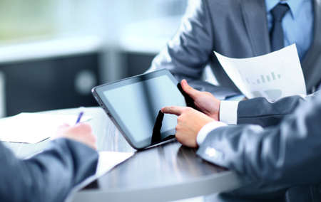 Obchodník drží digitální tablet na zasedání