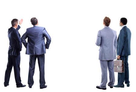 quattro mans affari dal retro - guardando qualcosa su uno sfondo bianco
