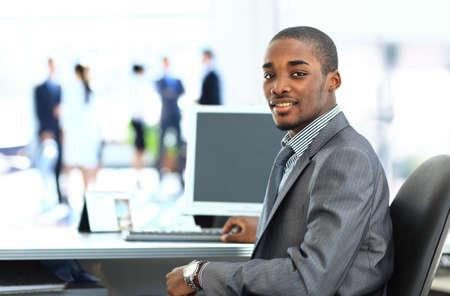 Portret van glimlachende Afro-Amerikaanse zakenman met leidinggevenden die werkzaam zijn in de achtergrond