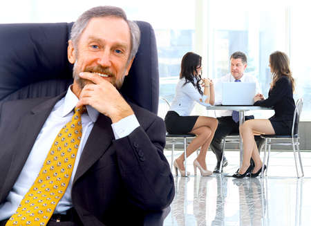 office staff: Successful business man standing with his staff in background at office Stock Photo