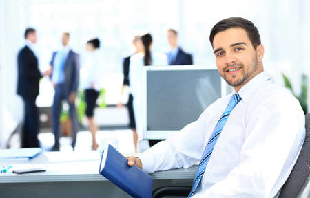 Portrait of smiling businessman working in office, looking camera Stock Photo