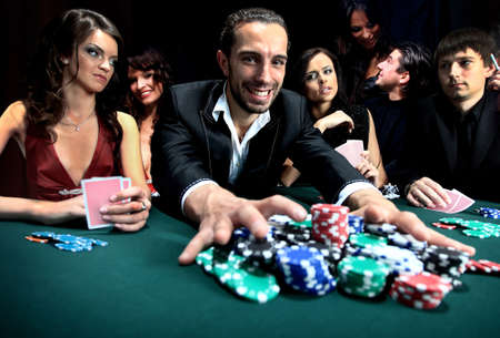 Poker player going all in pushing his chips forward Stock Photo