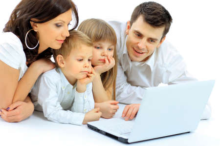 Loving family looking at a laptop lying down on bed at home photo