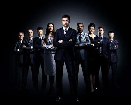 暗い背景上のビジネスのチームに立って