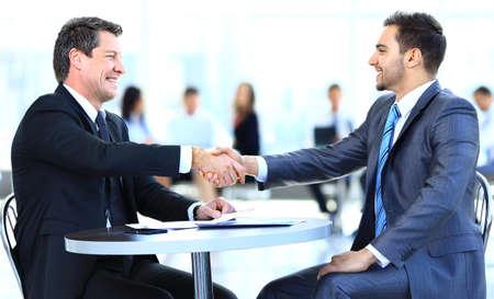 Business-Kollegen sitzen an einem Tisch während eines Treffens mit zwei männlichen Führungskräfte Händeschütteln Lizenzfreie Bilder