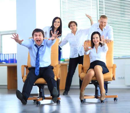 Empleados de oficina felices que se divierten en el trabajo en una carrera de silla de oficina Foto de archivo