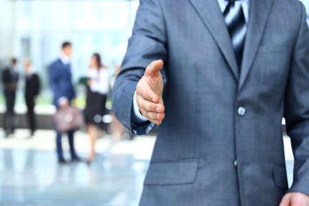 business handshake: Businessman extending hand to shake