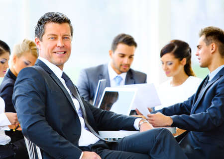 Portrait of young handsome businessman in office with colleagues in the background photo