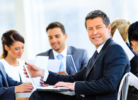 Portrait de jeune beau affaires dans le bureau avec des collègues dans l'arrière-plan