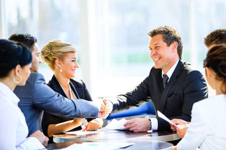 lideres: Empresario maduro estrechar la mano para sellar un acuerdo con su socio y colegas en una oficina moderna