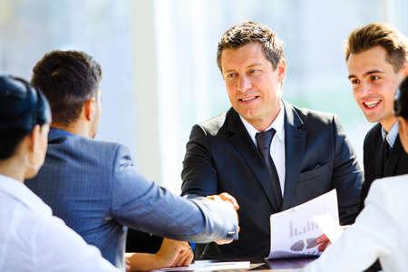 collègues d'affaires assis à une table lors d'une réunion avec deux cadres masculins serrant la main