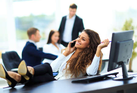 office phone: Photo of smiling brunette businesswoman with legs on the desk phoning in office