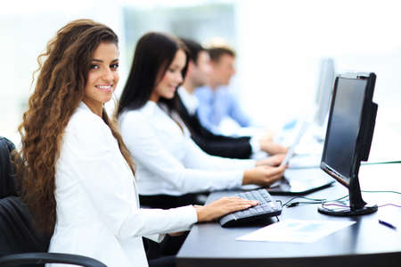 looking behind: Happy young businesswoman looking behind and her colleagues working at office Stock Photo