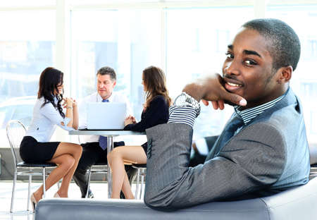 african american woman business: Portrait of smiling African American business man with executives working in background Stock Photo
