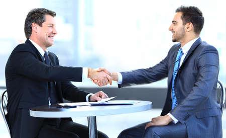 dando la mano: Colegas de negocios sentado en una mesa durante una reunión con dos ejecutivos hombres dándose la mano Foto de archivo