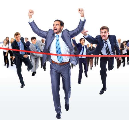 Happy businessman running through finishing line photo