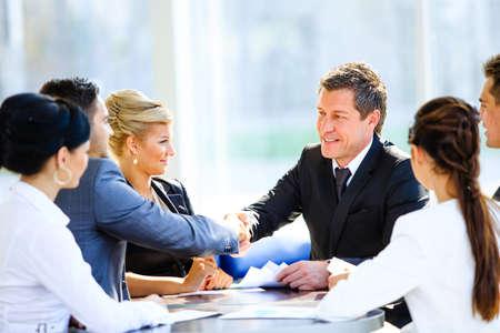Collega's zitten aan een tafel tijdens een vergadering met twee mannelijke leidinggevenden handen schudden