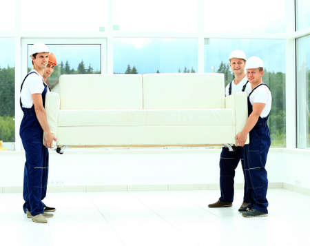 worker man: happy male movers in uniform carrying white sofa