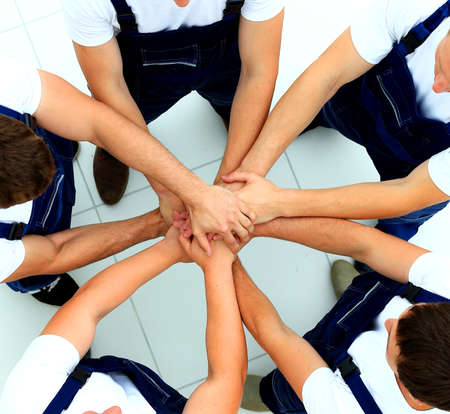 joining hands: team of workers joining hands in circle Stock Photo