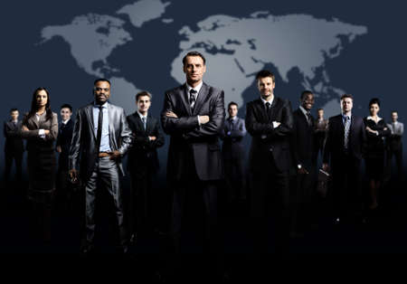 business partners: business team formed of young businessmen standing over a dark background Stock Photo