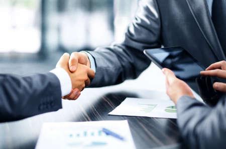 negócio: Empresários apertando as mãos
