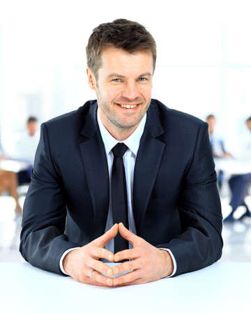 american banker: Portrait of smiling businessman sitting at a table of the background of his team