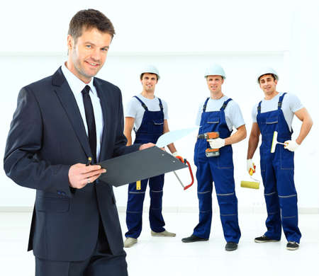 corporate office: young smiling owner on the background of the decorators holding construction tools Stock Photo