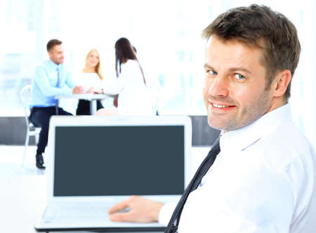 businessman working at his computer: businessman looking at the camera and smiling working at the computer. At the background-  his team