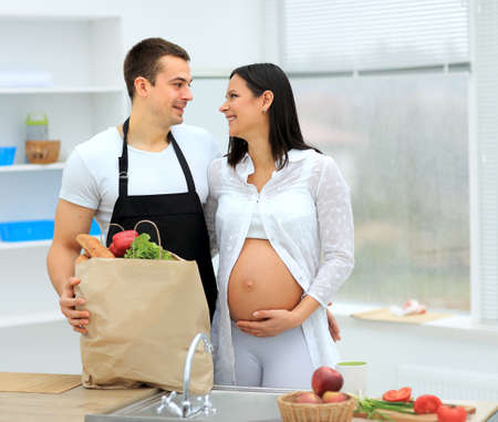 lovingly: man looks lovingly at his pregnant wife in the background of the kitchen
