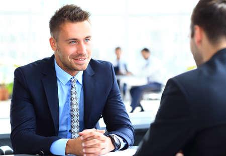 Imagem do homem de negócios inteligente explicando nova estratégia para seu sócio na reunião