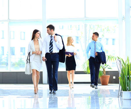 colleagues: businesspeople group walking at modern bright office interior Stock Photo