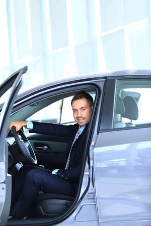 drive car: Young man choosing car at salon