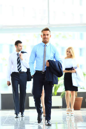 white people: businesspeople group walking at modern bright office interior Stock Photo