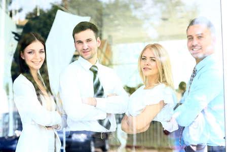 through window: Happy smiling business team looking through window