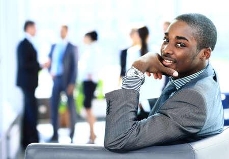 manos juntas: Retrato de sonriente hombre de negocios estadounidense con los ejecutivos que trabajan en segundo plano