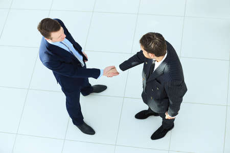two on top: Top view of a two businessman shaking hands - Welcome to business