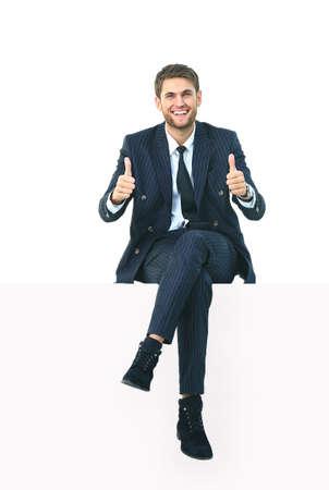 白の上に座っているハンサムな若いビジネスマン 写真素材