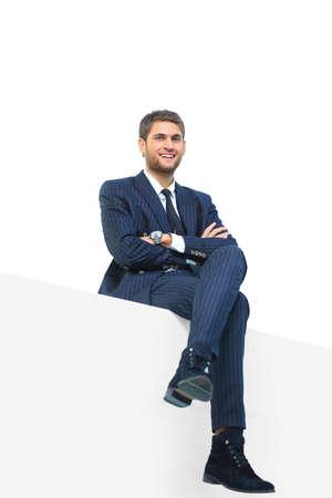 hombre sentado: apuesto hombre de negocios joven sentado en una tapa blanca Foto de archivo