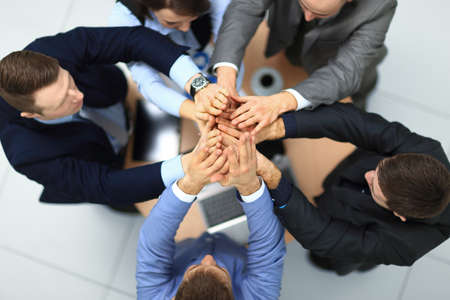 success and winning concept - happy business team giving high five in office. top view 스톡 콘텐츠