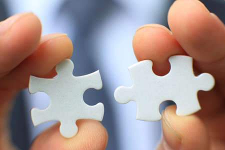 Businessman holding two blank white puzzle pieces in his hands conceptual of solving a problem, growth and development. Stock Photo