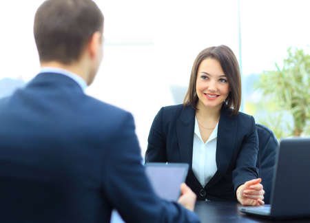 Beautiful young businesswoman conducting a job interview seated at her desk photo