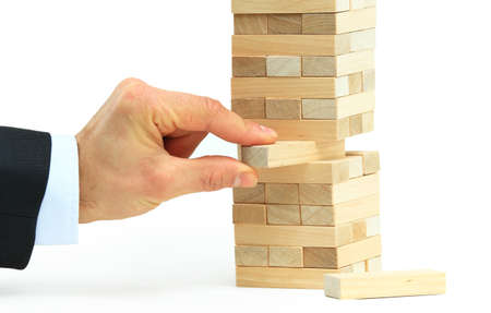 tower block: The tower from wooden blocks and mans hand take one block Stock Photo