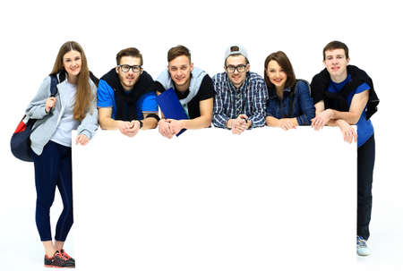 Full length portrait of confident college students displaying blank billboard against white background