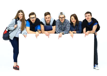 displaying: Full length portrait of confident college students displaying blank billboard against white background